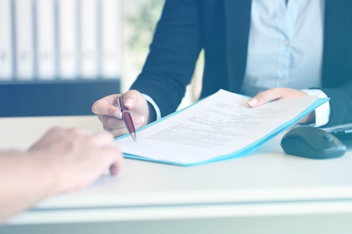 Mulher segurando caneta e documento, apontando para lugar da assinatura