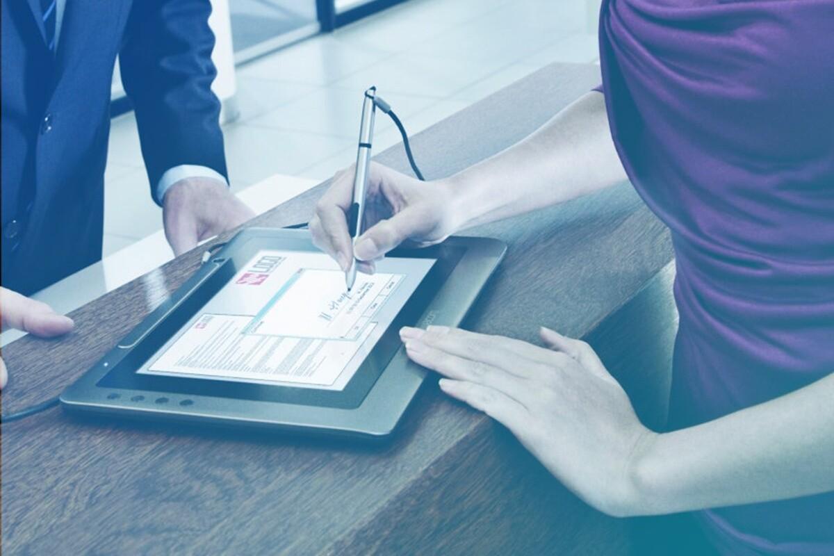 Mulher assinando em um tablet com uma caneta