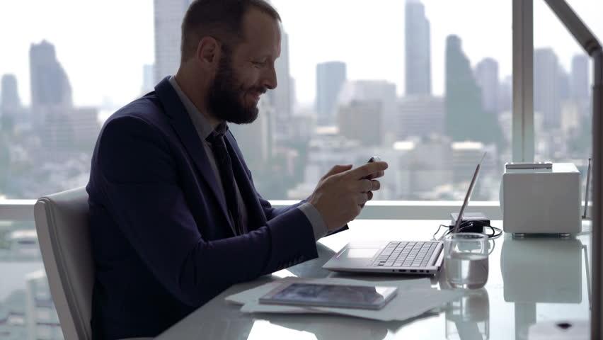 Homem mexendo no celular em sua mesa de trabalho
