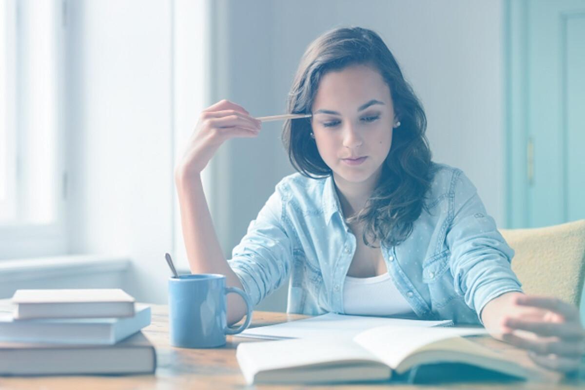 Mulher apoiando lápis sobre a testa enquanto lê livro