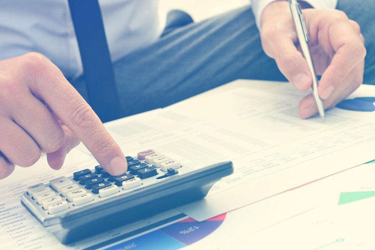 Homem mexendo na calculadora enquanto faz anotações