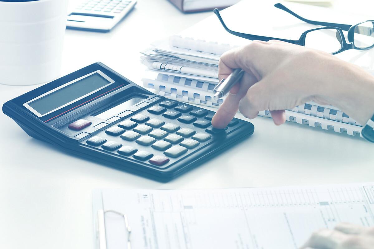 Pessoa mexendo na calculadora enquanto segura caneta
