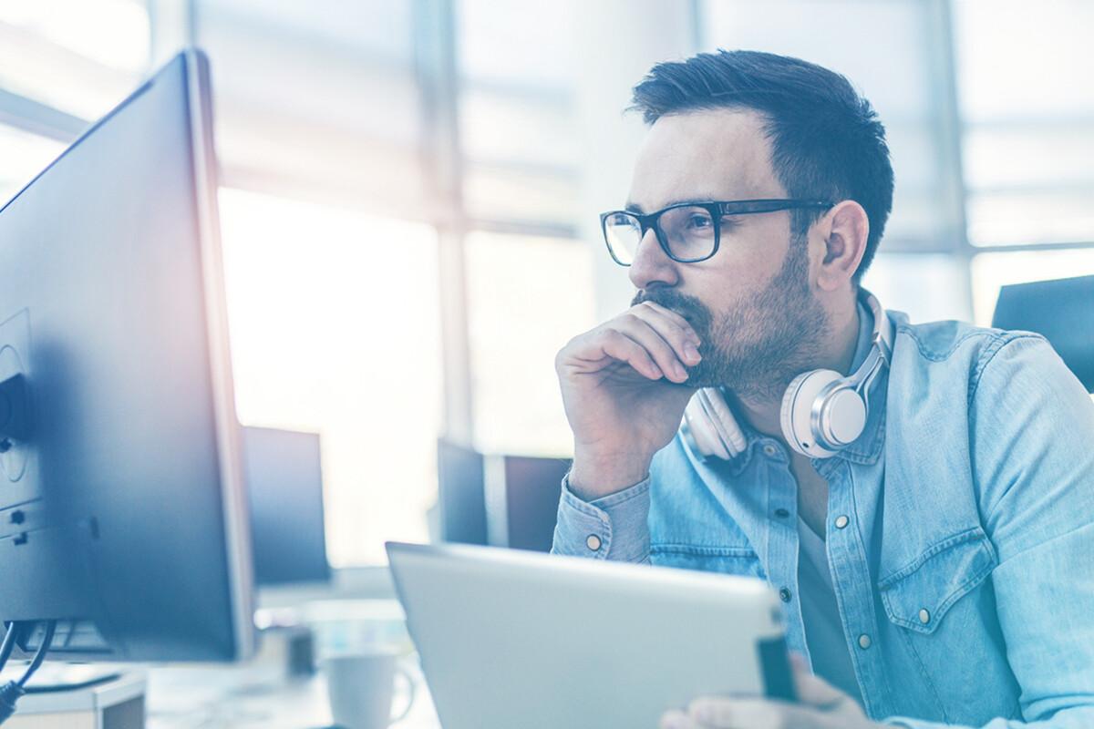 Homem com fone de ouvidos ao redor do pescoço segurando tablet e olhando para tela do computador