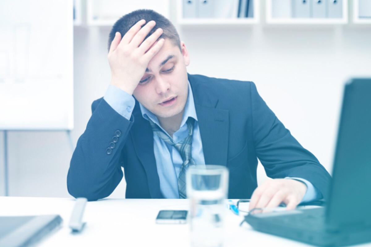 Homem cansado olhando para a mesa de trabalho