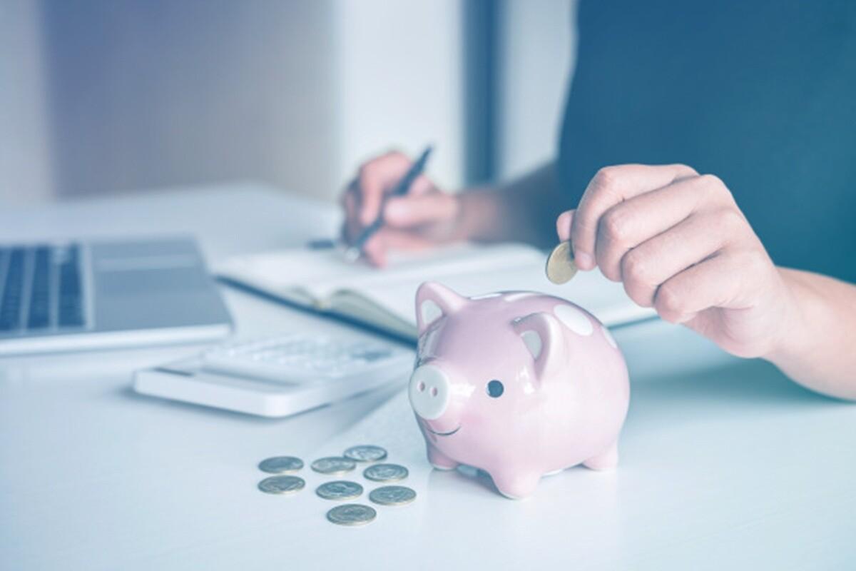 Pessoa segurando moeda e prestes a colocá-la em porquinho enquanto faz anotações