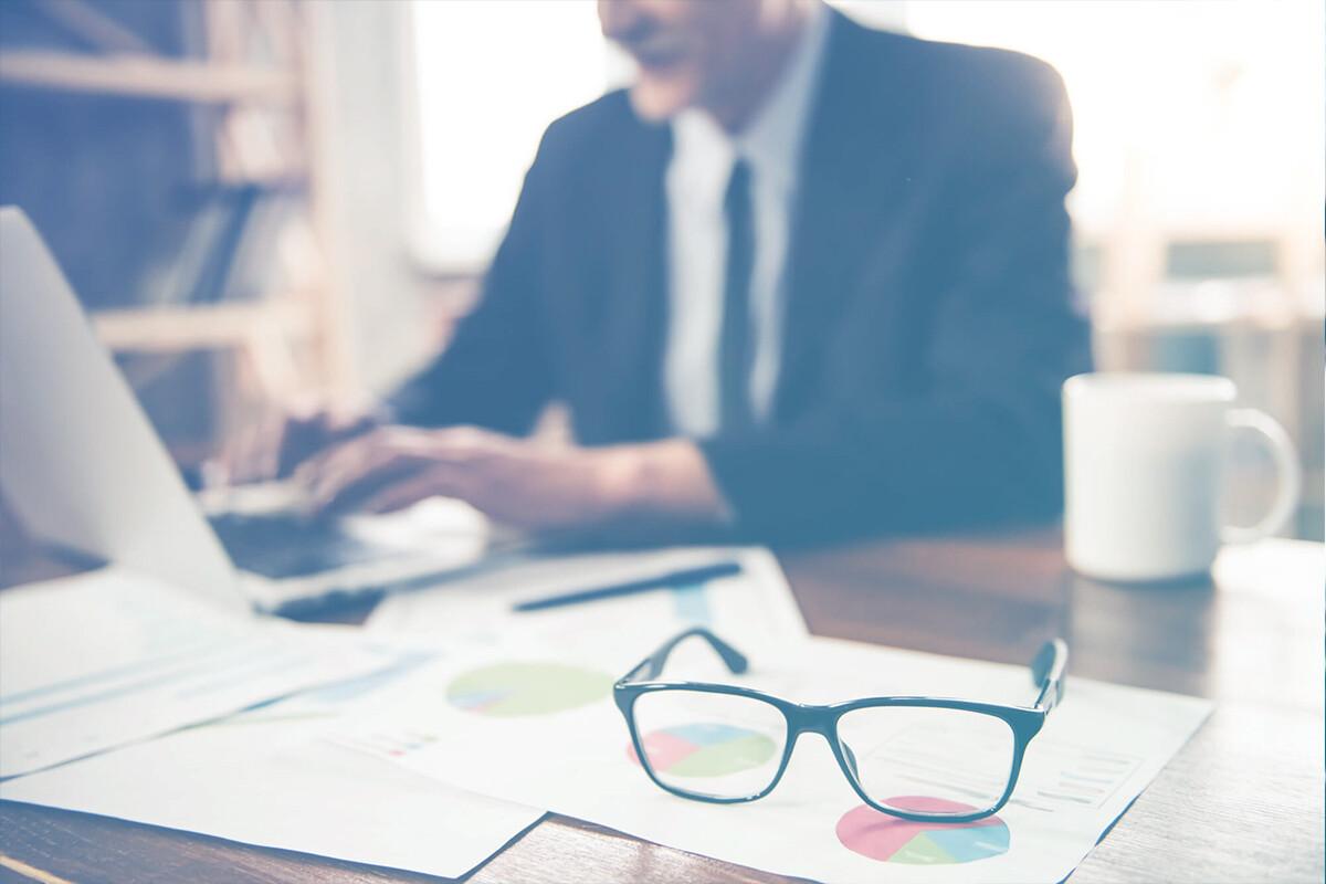 Homem trabalhando no notebook com papeis de gráficos sobre a mesa