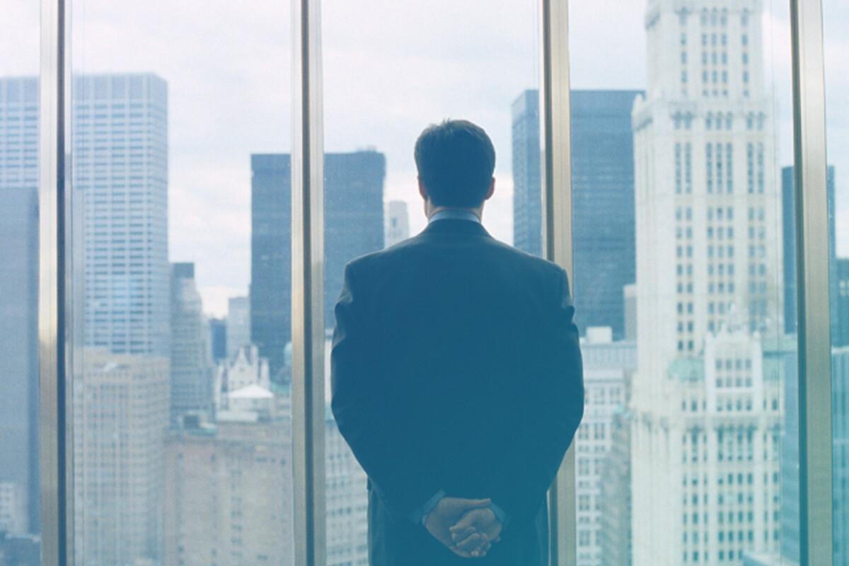 Homem de costas observando prédios pela janela