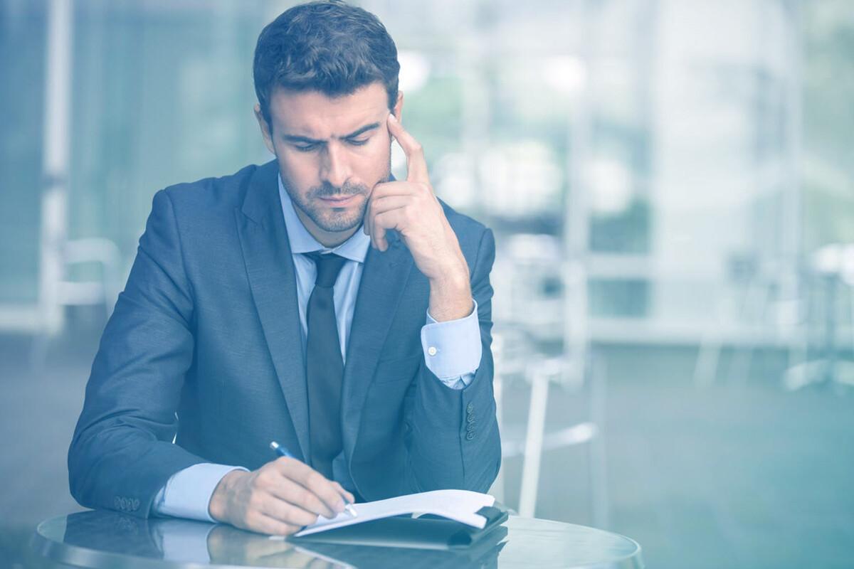 Homem olhando pensativo para documento