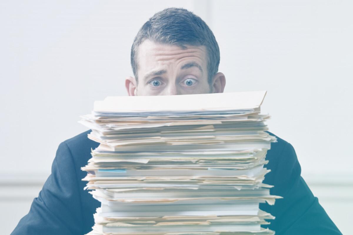 Homem olhando transtornado para pilha de documentos