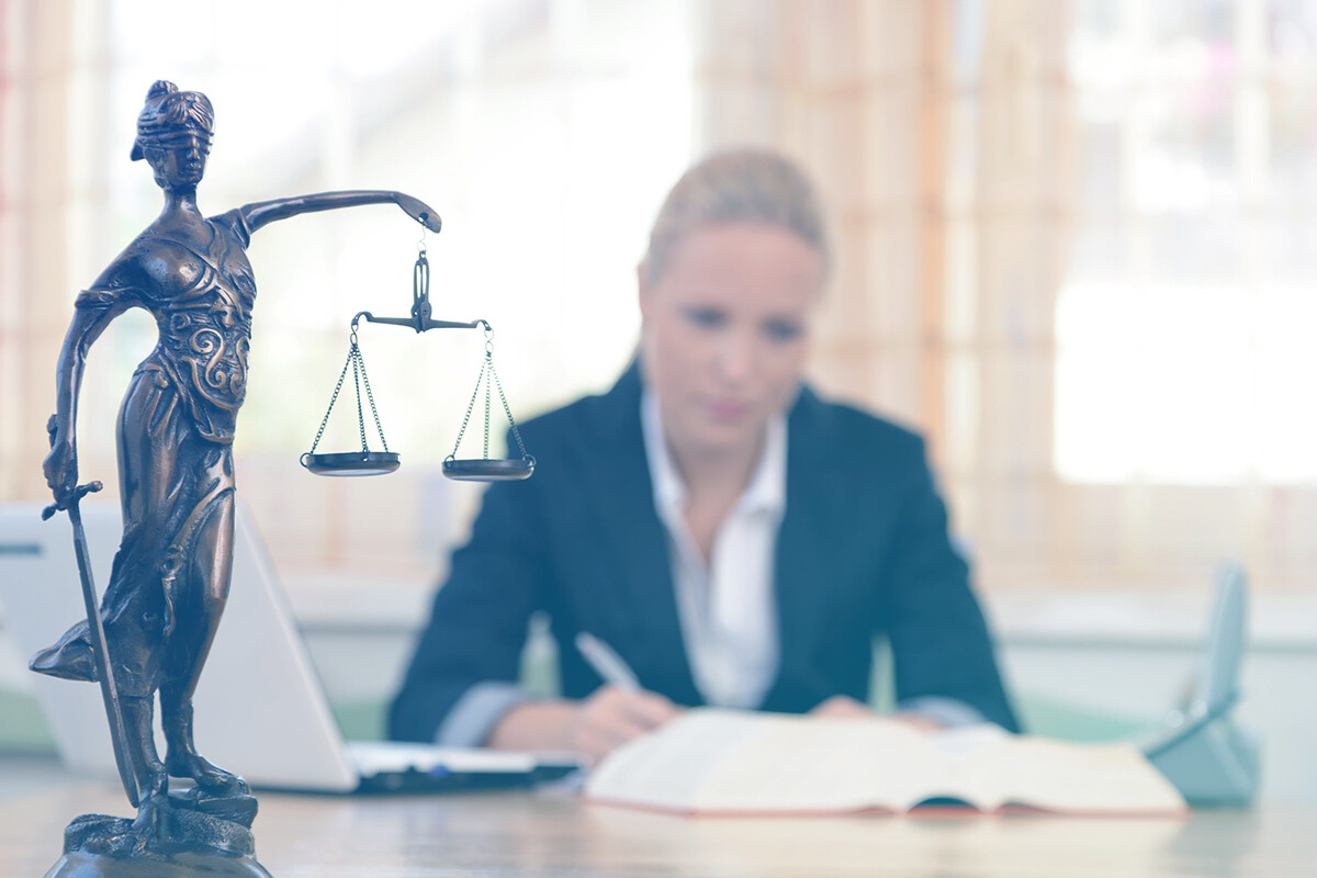 Advogada trabalhando com deusa da justiça à frente