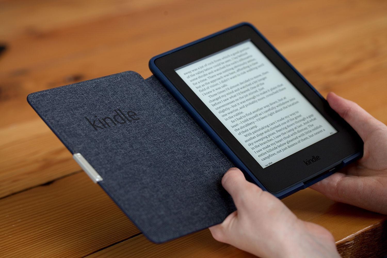 Pessoa segurando Kindle com livro aberto na tela