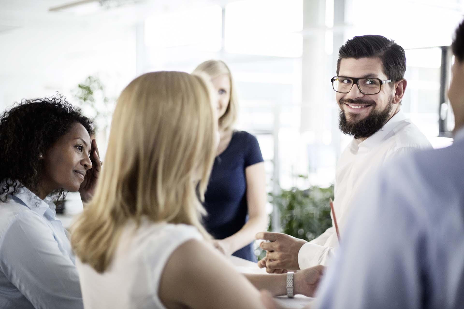 Homem sorrindo em grupo de colegas de trabalho