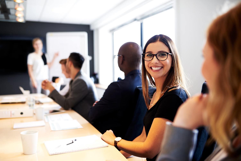 Mulher de óculos feliz em mesa de reunião do trabalho