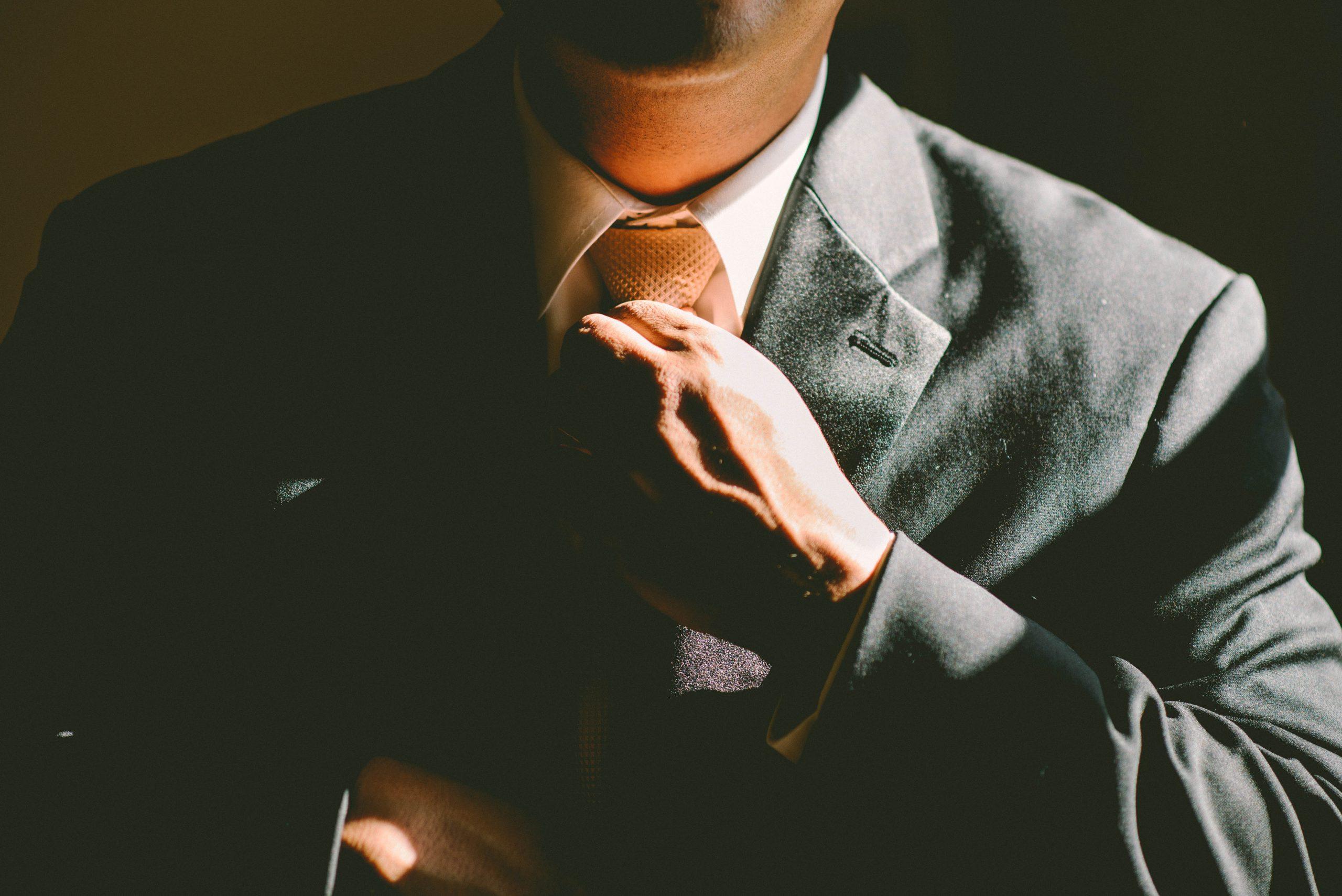 Homem de terno mexendo na gravata