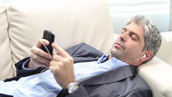 Advogado deitado no sofá com fones de ouvindo e mexendo no celular