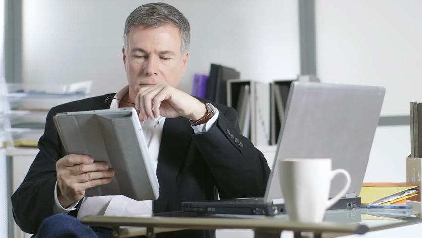Homem lendo no tablet em sua mesa de trabalho