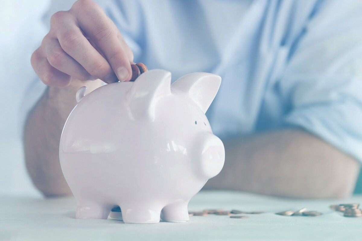 Homem colocando moeda no porquinho