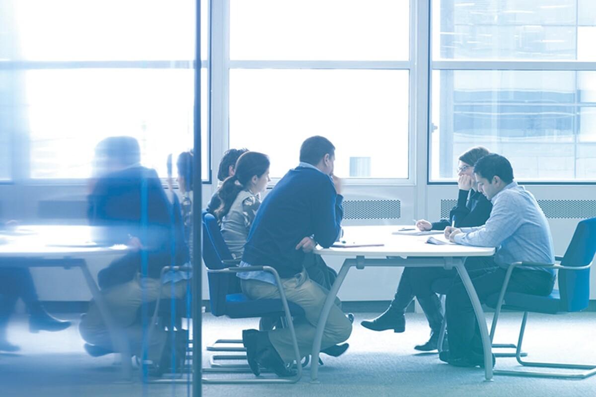 Pessoas trabalhando em mesa no ambiente corporativo