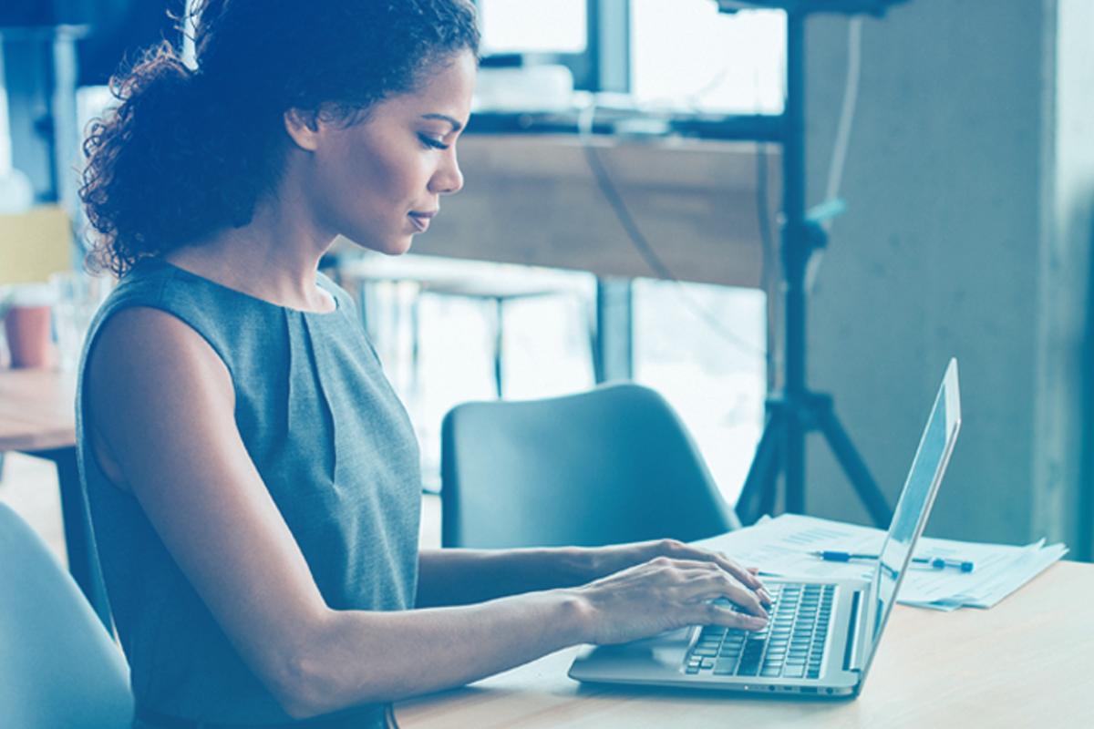 Imagem de mulher no computador representando o texto Esse tal de ROI pode ajudar seu escritório – aprenda a calcular