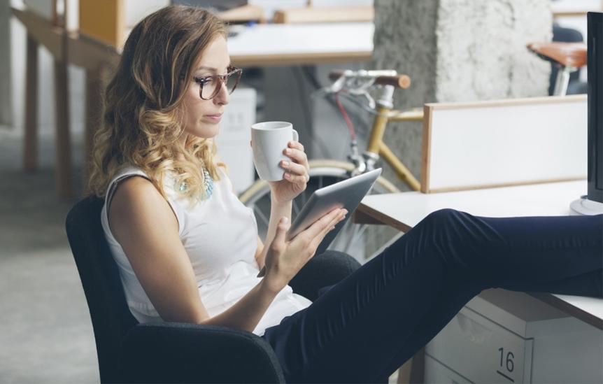 Mulher lendo tablet enquanto toma café