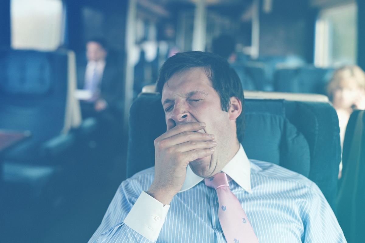 Homem bocejando sentado no trem