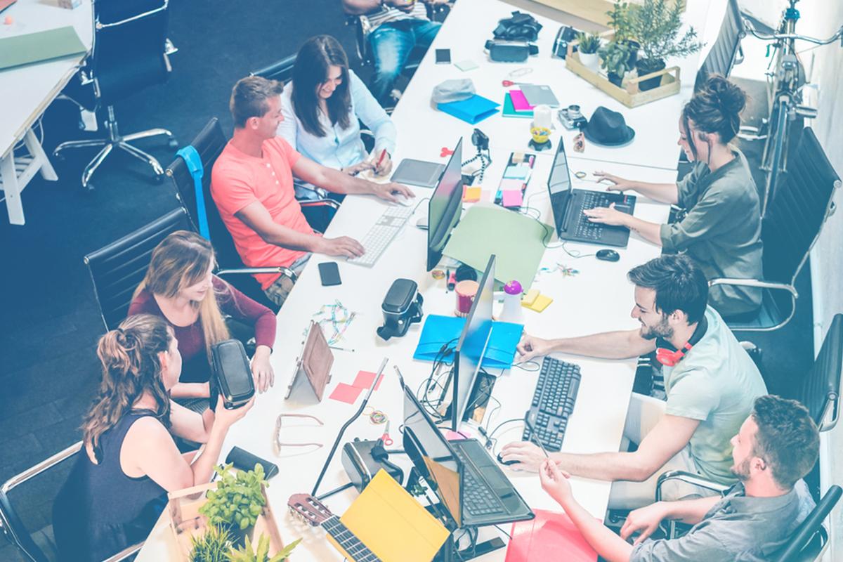 Várias pessoas reunidas sentadas ao redor de uma mesa
