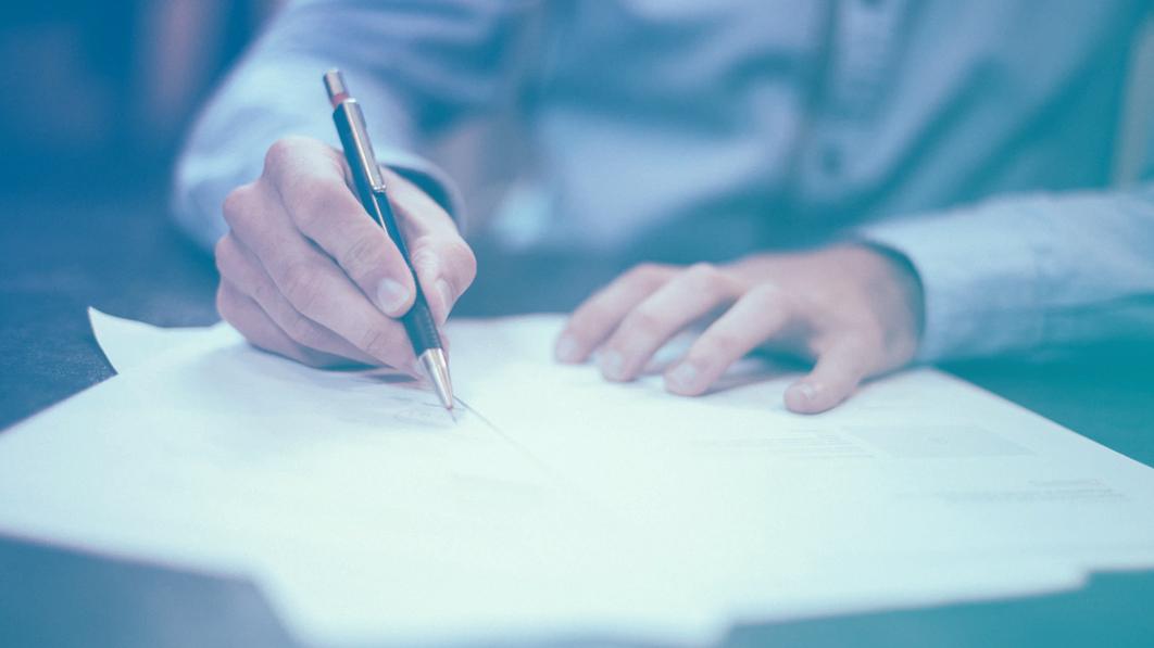 Homem segurando caneta e assinando documentos