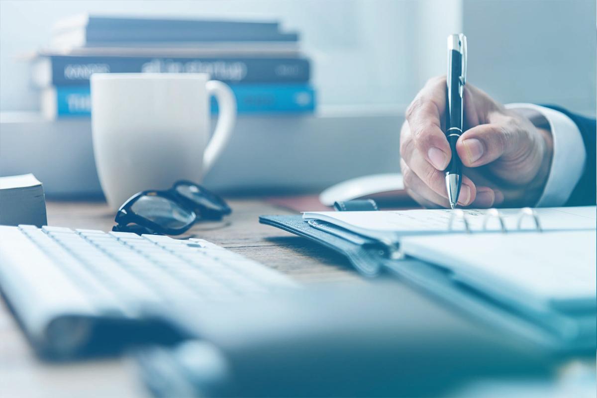 Homem segurando caneta e fazendo anotações com xícara e óculos sobre a mesa