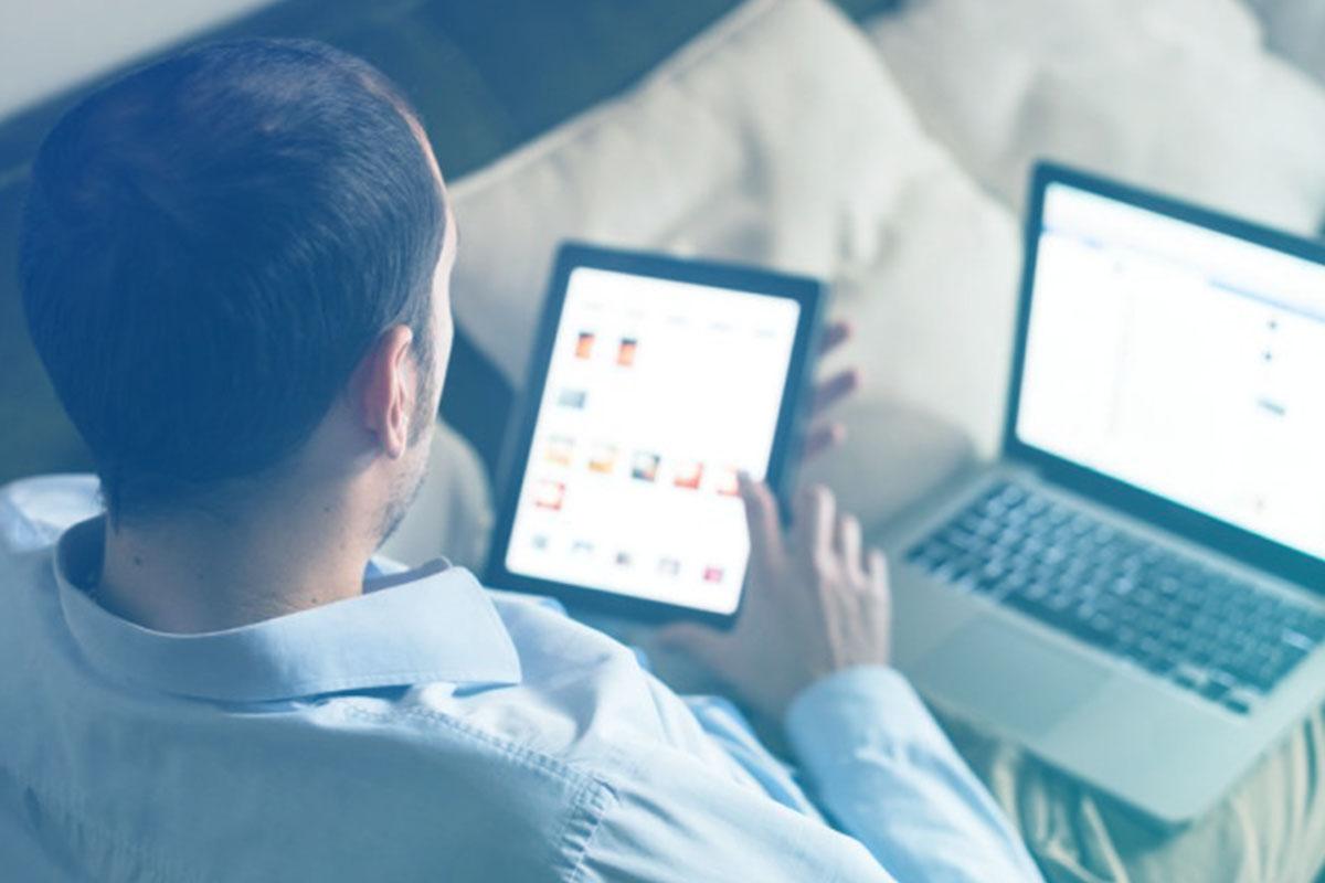 Homem de costas usando tablet com notebook no colo