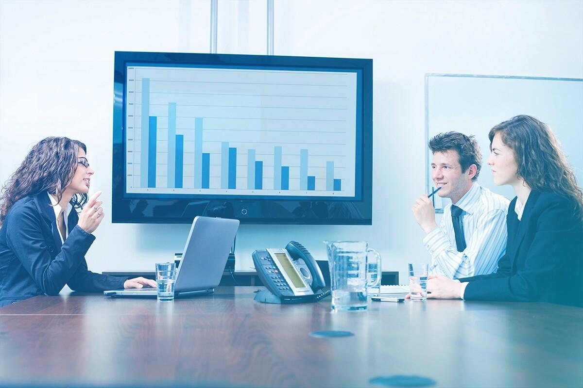 Pessoas sentadas à mesa com televisão expondo gráficos ao fundo