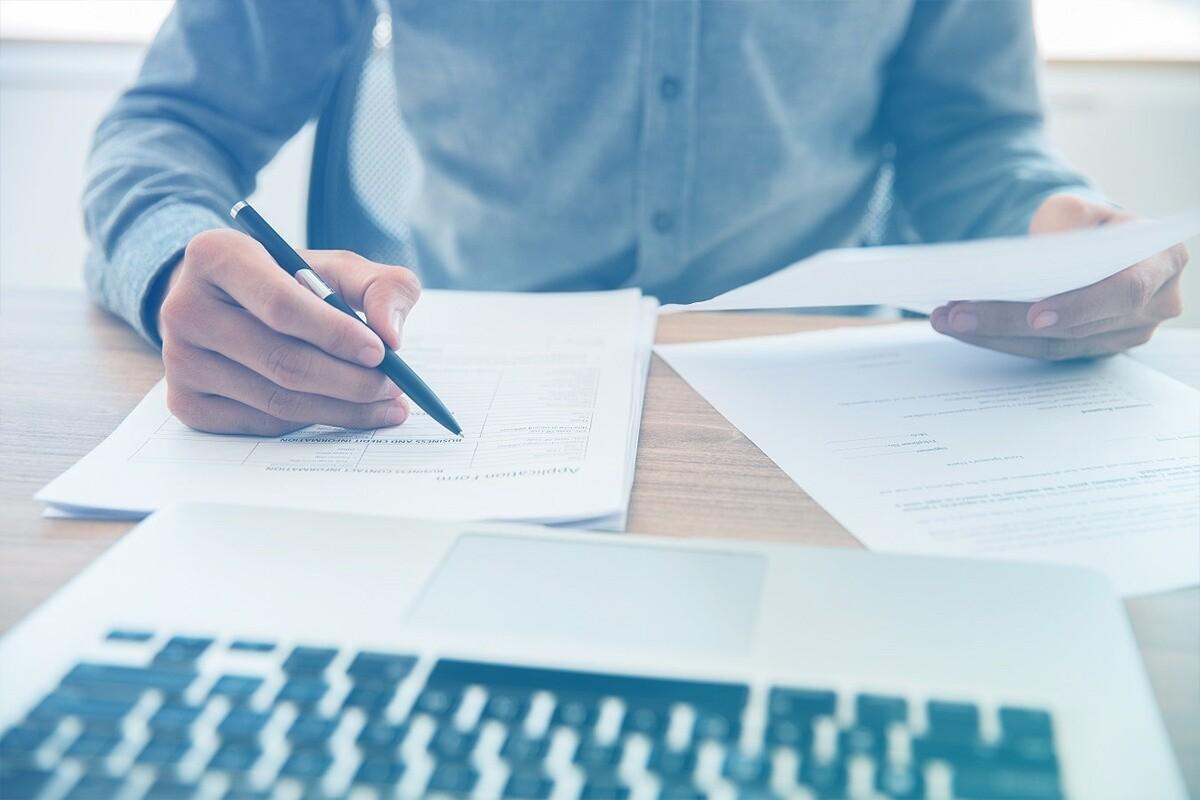 Homem segurando caneta e analisando documentos