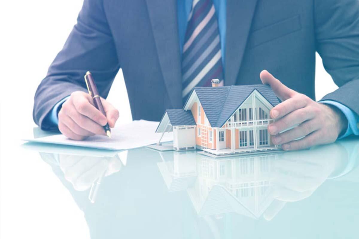 Advogado assinando documento com maquete de casa sobre a mesa