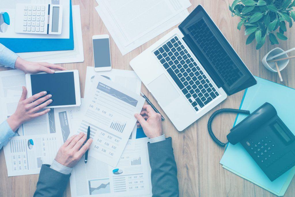 Pessoas trabalhando em mesa com papeis, notebook e tablet