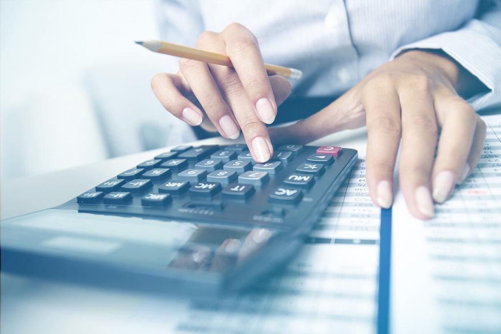 A imagem mostra duas mãos femininas, onde a direita segura um lápis e maneja uma calculadora ao mesmo tempo, enquanto a esquerda permanece sobre um papel.