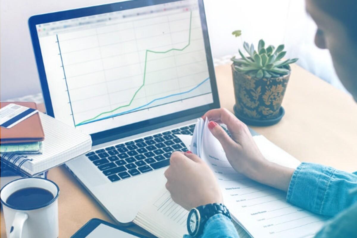 Pessoa mexendo em papeis com notebook mostrando gráfico