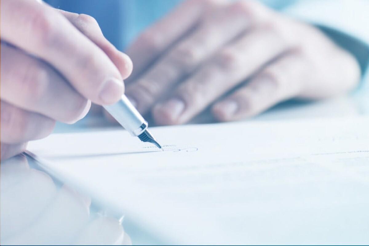 mãos com uma caneta na mão escrevendo em uma folha