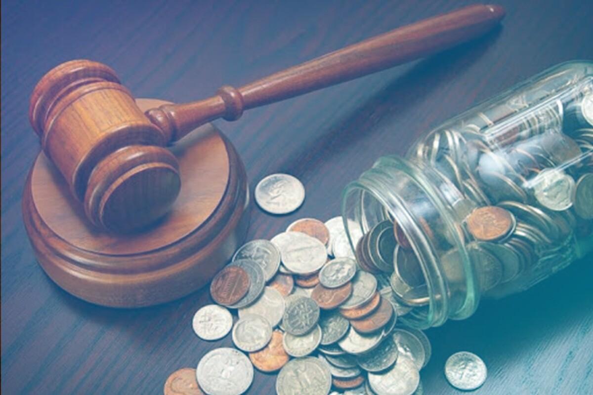 pote com moedas jogado em cima da mesa ao lado de um martelo do direito