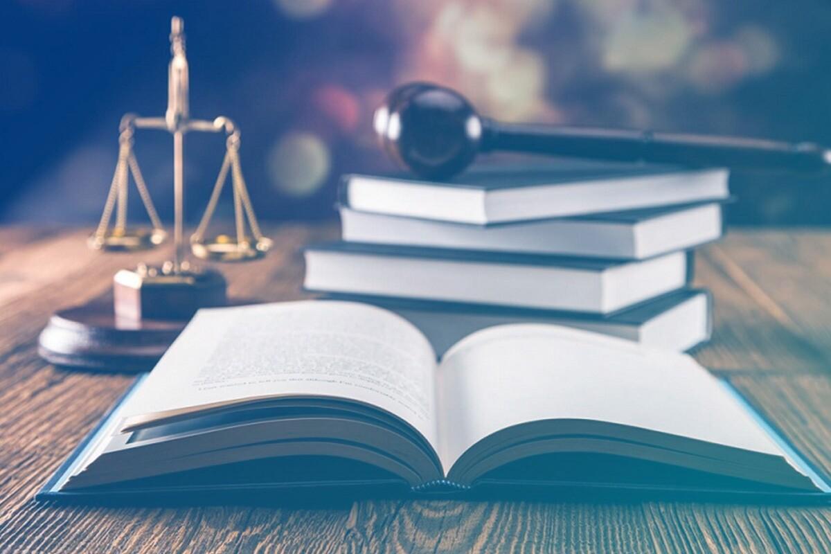 imagem de livros jurídicos em cima da mesa de madeira com Themis é um símbolo do direito