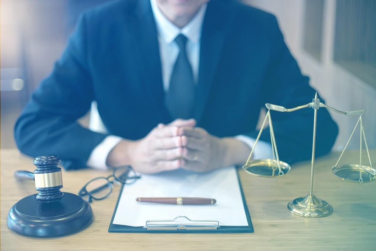Advogado sentado à mesa com documento, caneta, malhete e balança da justiça a sua frente