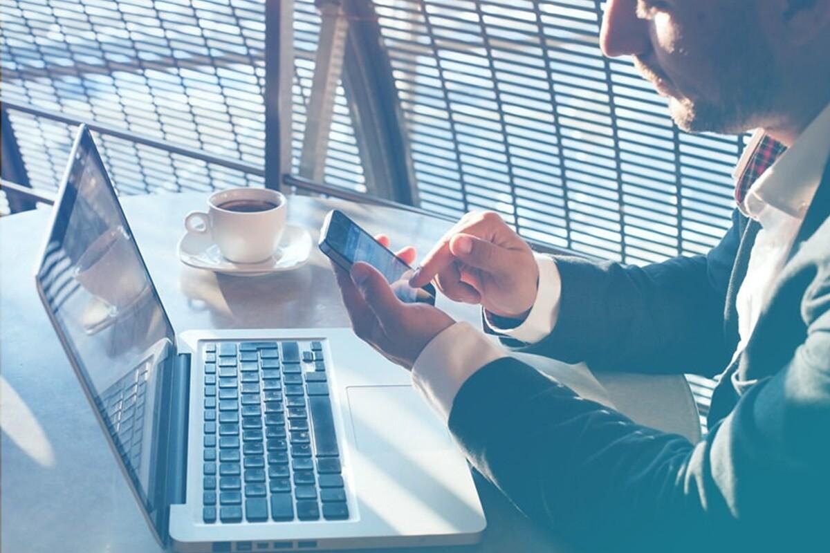 homem segurando celular na mão sentado em frente a um notebook que está em cima de uma mesa