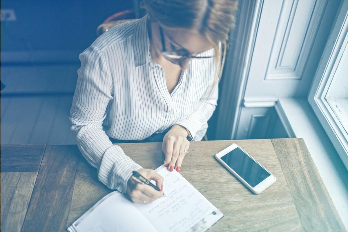 mulher sentada na cadeira escrevendo em um papel em cima da mesa, com o celular ao lado