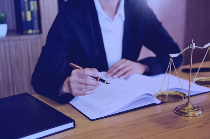 advogada segurando caneta com livro sobre a mesa