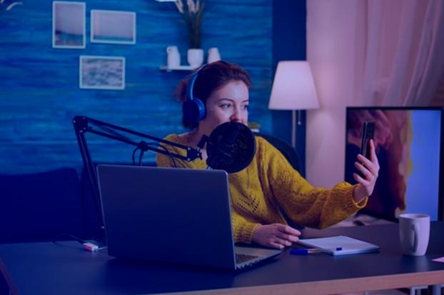 mulher no estúdop com computador e microfone gravando vídeo no celular